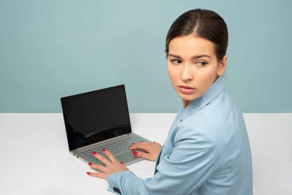 woman holding laptop computer while facing backward