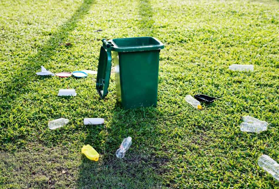 green trash bin on green grass field