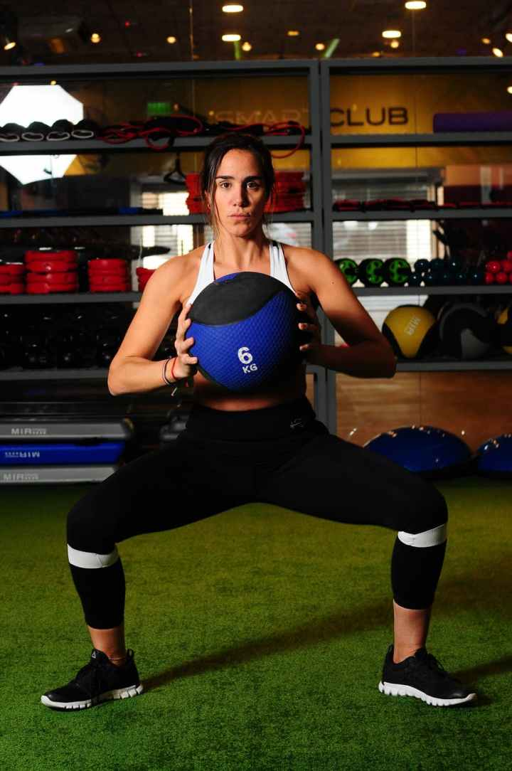 woman squatting holding medicine ball